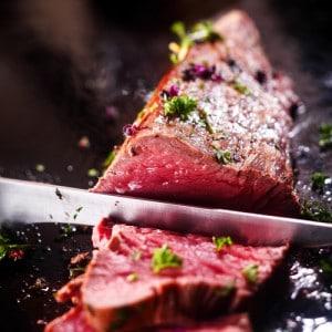 Mit Kräutern und Salz gewürztes Roastbeef, das mit einem Ausbeinmesser in Scheiben geschnitten wird