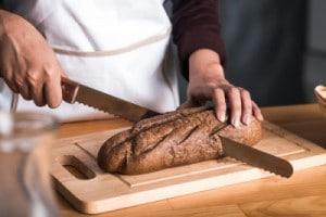 Frauenhände, die mit einem Brotmesser ein Roggenbrot schneiden