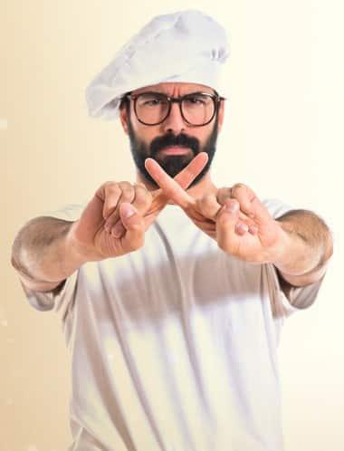 Koch in weißem T-Shirt und weißer Kochmütze, der die Zeigefinger kreuzt