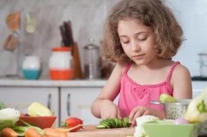 Mädchen beim Zerkleinern von Gemüse mit Hilfe eines Kindermessers
