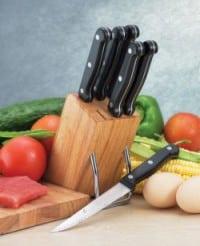 Messerblock aus Holz mit sechs Messern, umgeben von frischem Gemüse, einem Stück Fleisch sowie einem Holzbrett