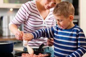 Mutter und Kind kochen zusammen Spaghetti Bolognese in der Küche